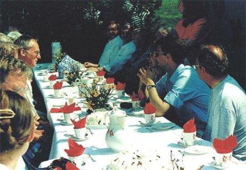 Prinseparret, arkæologer, Nydamselskabets bestyrelse og gæster til sønderjysk kaffebord i haven til Nydamhuset.