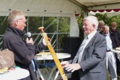 Formanden for Nydamselskabet overrækker A.P.Hansen sin gave, et sværd, kopi at et fra Nydam Mose.